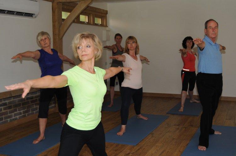 Students practising yoga in Guildford inside studio